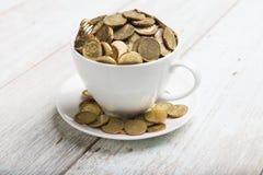 Tazza di caffè con le monete di oro Fotografie Stock