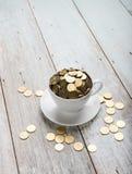 Tazza di caffè con le monete di oro Fotografia Stock