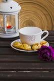 Tazza di caffè con le pasticcerie e la lampada sulla tavola di legno Fotografia Stock