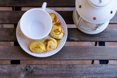 Tazza di caffè con le pasticcerie e la lampada sulla tavola di legno Fotografia Stock Libera da Diritti