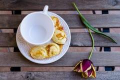 Tazza di caffè con le pasticcerie ed il fiore sulla tavola di legno Immagini Stock Libere da Diritti
