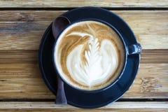 Tazza di caffè con luce solare di mattina sul fondo di legno della tavola fotografie stock libere da diritti