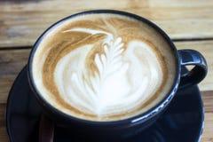 Tazza di caffè con luce solare di mattina sul fondo di legno della tavola fotografia stock