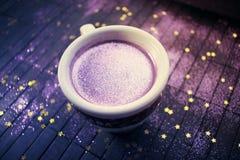 Tazza di caffè con scintillio porpora su fondo scuro con dorato Fotografie Stock