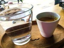 Tazza di caffè con un bicchiere d'acqua su un vassoio con il cucchiaio fotografia stock libera da diritti