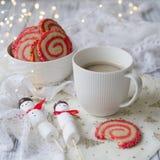 Tazza di caffè con un pupazzo di neve della caramella gommosa e molle ed i biscotti sotto forma di spirale nella tavola di Natale immagini stock libere da diritti