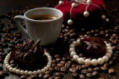 Tazza di caffè con una collana del regalo ed i chicchi di caffè nel backgroun immagini stock libere da diritti