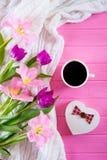 Tazza di caffè, contenitore di regalo nella forma di cuore e mazzo tenero di bei tulipani su fondo di legno rosa Fotografia Stock