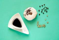 Tazza di caffè creativa e ciambella lustrata di bianco con i dolci neri del cioccolato sul fondo della menta Concetto dell'alimen Fotografia Stock