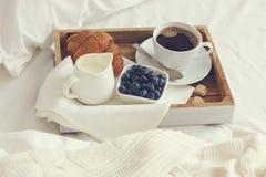 Tazza di caffè, croissant e mirtillo fresco sul vassoio di legno, bre fotografia stock libera da diritti