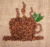 Tazza di caffè dai fagioli con le foglie sul fondo della tela di sacco Fotografie Stock Libere da Diritti