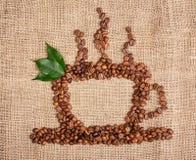 tazza di caffè dai fagioli sul fondo della tela di sacco Fotografie Stock