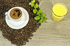 Tazza di caffè, dei chicchi di caffè, del succo di orango e delle foglie di tè freschi della menta Fotografia Stock