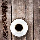 Tazza di caffè del caffè espresso e chicchi di caffè arrostiti su vecchio tabl di legno Fotografia Stock