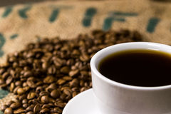 Tazza di caffè del caffè macchiato, su un sacco del caffè con i semi di cacao torrefatti Fotografie Stock