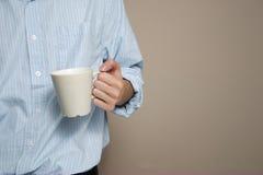 Tazza di caffè della holding dell'uomo Fotografie Stock