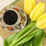 Tazza di caffè della porcellana con i fiori gialli del tulipano Fotografie Stock Libere da Diritti