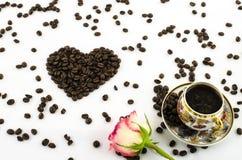 Tazza di caffè della porcellana con il cuore rosa dei chicchi di caffè e del fiore Fotografia Stock Libera da Diritti