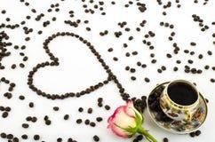 Tazza di caffè della porcellana con il cuore rosa dei chicchi di caffè e del fiore Immagini Stock Libere da Diritti