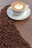 Tazza di caffè di arte del latte con i chicchi di caffè su fondo di legno Immagine Stock