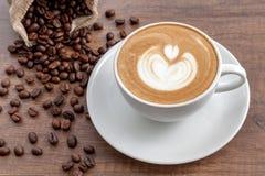 Tazza di caffè di arte del latte con i chicchi di caffè su fondo di legno Immagini Stock