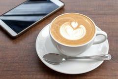 Tazza di caffè di arte del latte con lo smartphone su fondo di legno Fotografia Stock