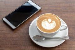 Tazza di caffè di arte del latte con lo smartphone su fondo di legno Fotografia Stock Libera da Diritti