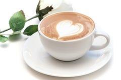Tazza di caffè di arte del latte di forma del cuore sul piatto con la rosa di bianco Fotografia Stock Libera da Diritti