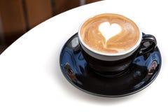 Tazza di caffè di arte del latte di forma del cuore sulla tavola in caffetteria Fotografia Stock