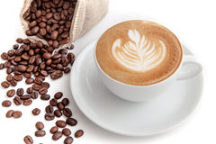 Tazza di caffè di arte del latte di rosetta con i chicchi di caffè accanto, sul whi Immagini Stock Libere da Diritti