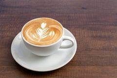 Tazza di caffè di arte del latte di rosetta su fondo di legno con lo spazio della copia Fotografia Stock