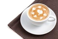 Tazza di caffè di arte del latte, molte forme del cuore sulla cima, posto su napk Fotografia Stock Libera da Diritti