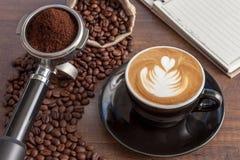 Tazza di caffè di arte del latte nella tazza nera di colore con un certo caffè Fotografia Stock Libera da Diritti