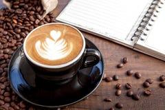 Tazza di caffè di arte del latte nella tazza nera di colore con un certo caffè Fotografia Stock
