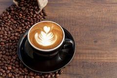 Tazza di caffè di arte del latte nella tazza nera di colore con un certo caffè Fotografie Stock