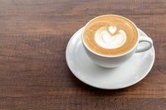 Tazza di caffè di arte del latte su fondo di legno con lo spazio della copia Fotografia Stock