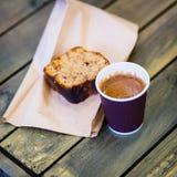 Tazza di caffè di carta con schiuma, pezzo di dolce di cioccolato, trovantesi sulla tavola di legno, vista superiore Tono d'annat Fotografie Stock