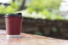 tazza di caffè di carta rossa sulla tavola di legno con il backgroun delle foglie verdi Fotografia Stock