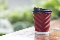 tazza di caffè di carta rossa sulla tavola di legno con il backgroun delle foglie verdi Fotografia Stock Libera da Diritti