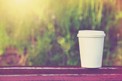 Tazza di caffè di carta sul fondo di mattina immagine stock libera da diritti