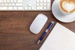 Tazza di caffè di forma del cuore di arte del latte sulla tavola di legno accanto con Fotografia Stock