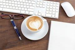 Tazza di caffè di forma del cuore di arte del latte sulla tavola di legno accanto con Immagini Stock Libere da Diritti