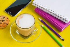 Tazza di caffè di mattina con il dolce ed i taccuini su una tavola Fotografia Stock Libera da Diritti