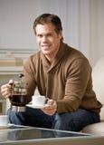 Tazza di caffè di versamento del carafe del caffè della holding dell'uomo immagini stock libere da diritti
