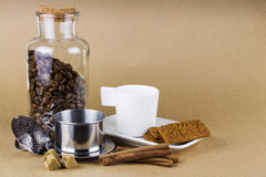 Tazza di caffè, dispositivo di gocciolamento, biscotti e un barattolo di vetro dei chicchi di caffè Immagine Stock