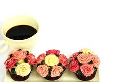 Tazza di caffè e bigné delle rose sopra fondo bianco Fotografia Stock