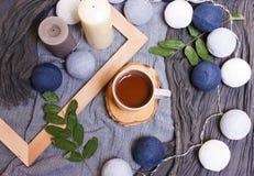 Tazza di caffè e candele, rami verdi, foglie su una b alla moda Fotografia Stock Libera da Diritti