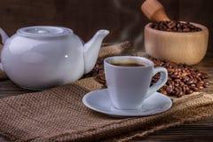 Tazza di caffè e chicchi di caffè con fumo sulla tavola Immagini Stock