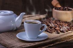 Tazza di caffè e chicchi di caffè con fumo sulla tavola Fotografia Stock