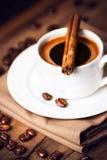 Tazza di caffè e chicchi di caffè con i bastoni di cannella sulla fronte di legno Fotografie Stock Libere da Diritti